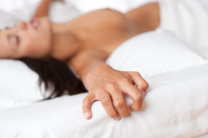 Naked woman lying in bed, focus on hand