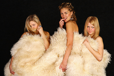 Three young girls hiding behind white fur.